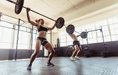 Fitness people at gym performing deadlift exercise with weight bar. Man and woman doing weightlifting exercises in gym. poster