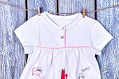 Childs top hanging on clothesline. Baby dress drying on rope on old wooden background. Kids apparel in laundry. poster