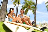 Hawaii surfers people lifestyle happy living couple talking on Waikiki beach relaxing from surfingwith surfboards in Honolulu city. Friends laughing having fun in Oahu island, USA travel lifestyle. poster