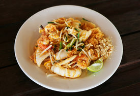 Thai style fried rice noodles and shrimps with egg, nuts and lime