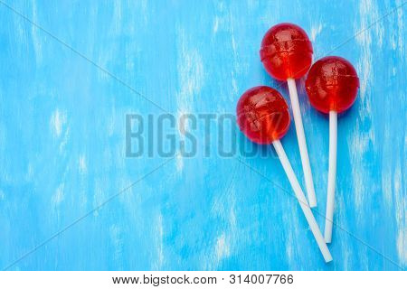 Three Ball Red Lollipops On White Sticks. Central Lollipop Above, At The Right Edge, On The Blue Bac