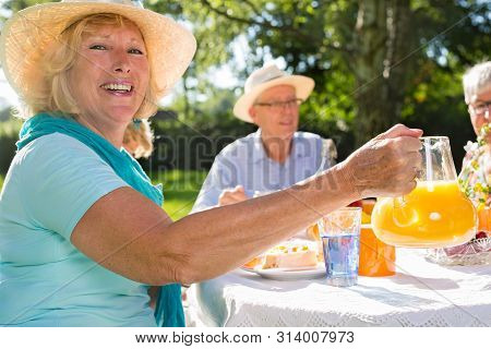 Seniors Having Picnick Outdoors In Sunshine, Blond Beautiful Woman With A Hat Is Serving Orange Juic