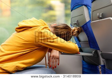 Woman In Orange Hoodie Sitting In A Seat And Sleeping On A Folding Table In Public Transportation. T