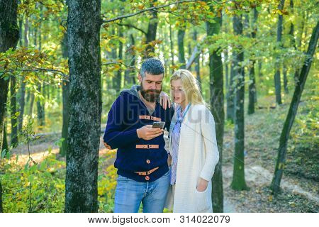Autumn Couple - Internet On A Phone Outdoors. Happy Couple On Autumn Walk. Outdoor Autumn Atmospheri