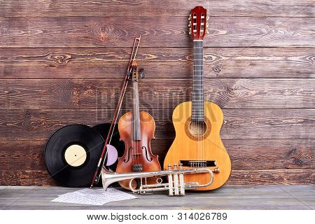 Retro Musical Instruments On Wooden Background. Acoustic Guitar, Trumpet, Violin, Vinyl Records And