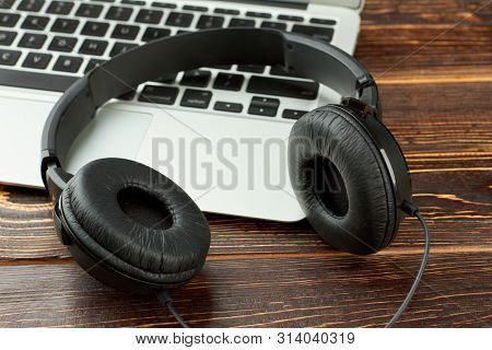 Black Leather Headphones And Laptop. Headphones And Silver Laptop Computer On Wooden Background. Mus