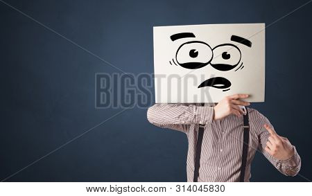 Casual person holding a paper with funny emoticon in front of her face