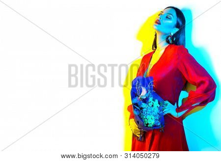 Beauty model girl posing in bright colorful multicolour lights with bunch of flowers, Fashion Art portrait of beauty young woman in studio holding bouquet of flowers, isolated on white background.