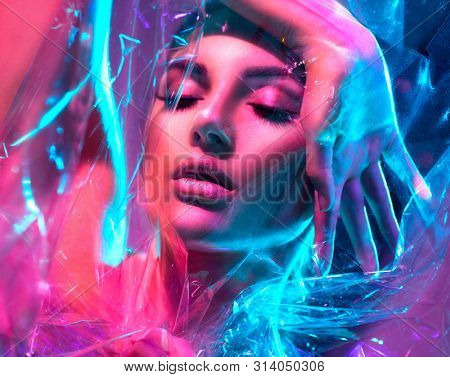 High Fashion model girl in colorful bright neon lights posing in studio through transparent film. Portrait of beautiful sexy woman in UV. Art design colorful make up. On colourful vivid background
