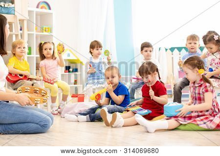 Group Of Kindergarten Children Play With Musical Toys. Early Musical Education In Day Care Centre