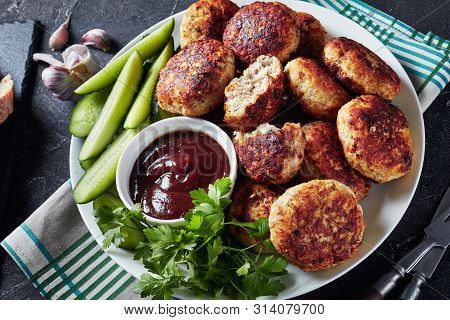 Polish Meat Rissoles Served With Cucumber Slices And Barbeque Sauce On A White Plate On A Concrete T