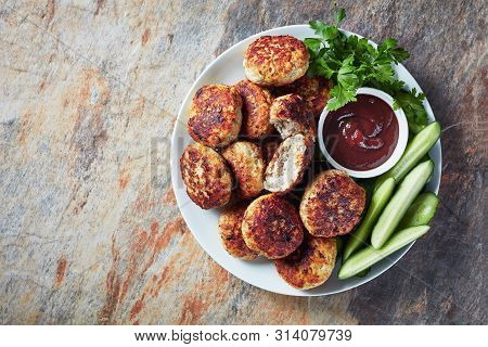 Polish Meat Rissoles Served With Cucumber Slices And Barbeque Sauce On A White Plate On A Table, Hor