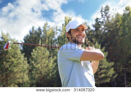 Golfer hits an fairway shot towards the club house. poster
