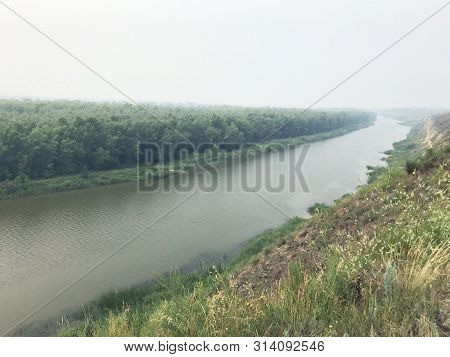 Landscape In The Mist. River On A Cloudy Day Against The Forest Shrouded In Fog