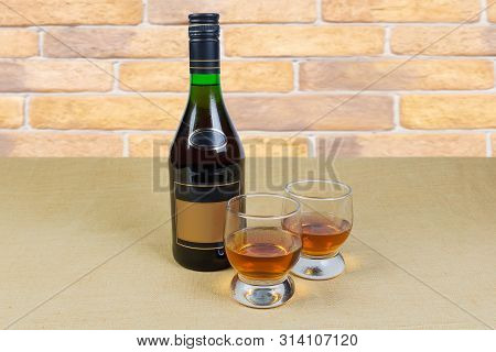 Two Portion Of Brandy In Brandy Bowls And Bottle Of Brandy On A Textile Surface