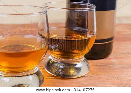Two Portions Of Brandy In Brandy Bowls On A Blurred Background Of Bottle Of Brandy On The Rustic Tab