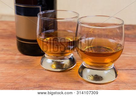 Two Portions Of Brandy In Brandy Bowls On A Background Of Brandy Bottle On The Rustic Table In Selec