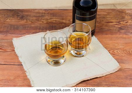 Two Portions Of Brandy In Brandy Bowls On Napkin On A Background Of Brandy Bottle On The Rustic Tabl