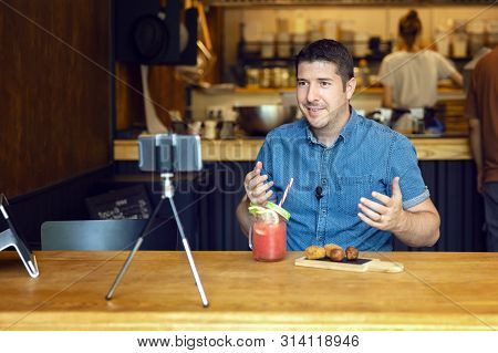 Social Media Influencer Or Food Blogger Creating Content Inside Small Restaurant - Man Sharing Onlin