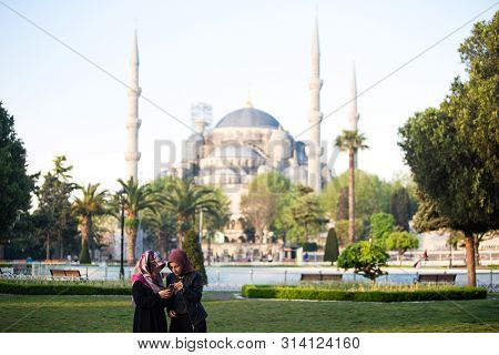 Turkey, Istanbul - May 3, 2019: Women In Hijab Look At The Phone On The Square Park In Front Of The