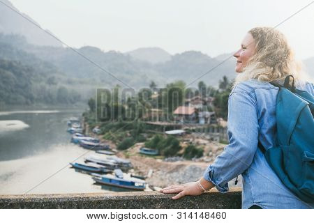Young Caucasian Blond Woman In A Denim Shirt Standing On The Bridge Over Nam Ou River During Sunset