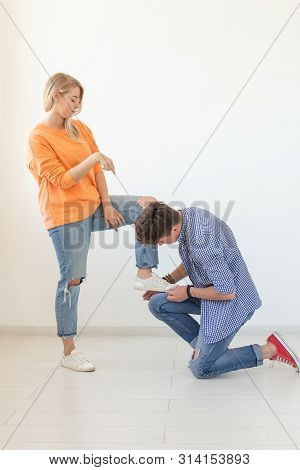 Young man tying shoelaces of his beloved woman posing on the white background. Concept of courtship and reverent relationships. poster