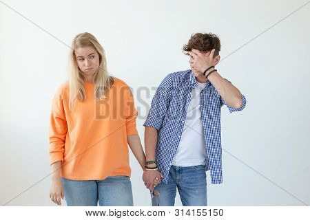 Young couple of students disgruntled boyfriend and tired young girlfriend posing on a white background holding hands. Concept of a crisis in relationships and the help of a psychologist. poster
