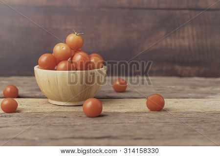Group Tomato In A Wood Bowl Place On The Wooden Table. Cherry Tomatoes Is A Small That Has A Sweet,