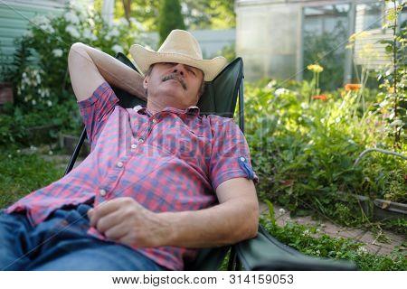 Senior Hispanic Man In Hat Sitting Leaning Back On Chair Sleeping In Outdoor Summer Flower Garden