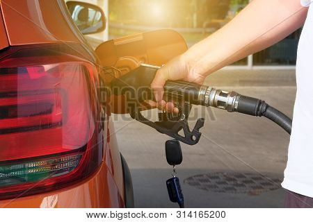 Petrol Station Pump. Pumping Gasoline Fuel In Orange Car At A Gas Station. To Fill Orange Car With F