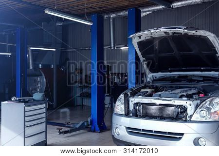 Silver Car With Open Hood At Service Station Garage. Modern Workshop Auto Repair Shop With Hydraulic