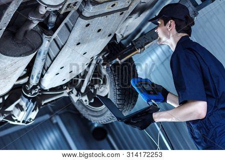 Mechanic Man In Blue Jumpsuit Is Repairing Car At Service Station Garage. Repairman Is Unscrewing Nu