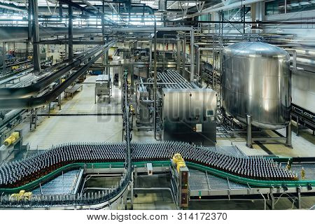 Automatic Modern Production Line At Brewery. Conveyor Line And Vats For Fermentation And Pasteurizat
