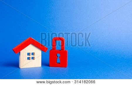 House Figurine And A Red Padlock. Security And Safety. Confiscation For Debts. Alarm System. Seizure
