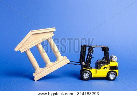 Yellow Forklift Overturns A Government Building. Bank, Museum, Monument Of Architecture. Dismantling