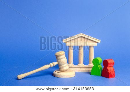 Two Figures Of People Opponents Stand Near The Courthouse And The Judge's Gavel. The Judicial System