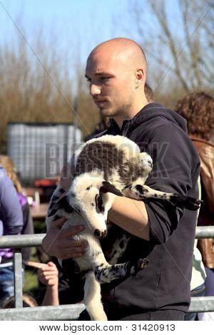 Man Holding A New Born Lamb