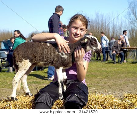A Young Girl Stroking A Brown And White New Born Lamb