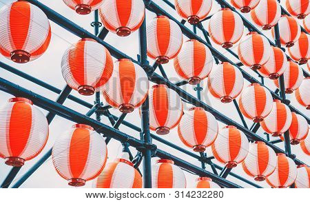 Many Paper Red-white Oriental Paper Lanterns Hanging In A Row On Blue Sky Background