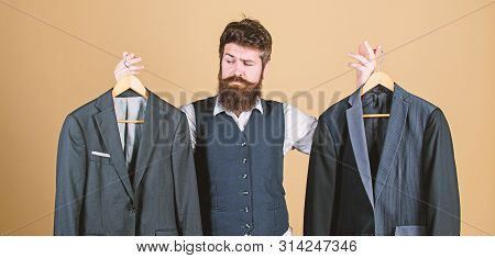 Doubting About His Choice. Bearded Man Holding Suit Jackets In Store, Choice Concept. Hipster Making