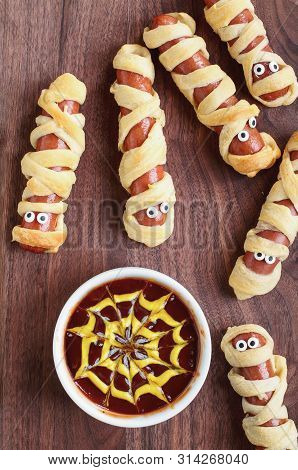 Fun Food For Kids. Mummy Hot Dogs Lying On A Rustic Table With A Bowl Of Ketchup And Mustard Dip, Wi
