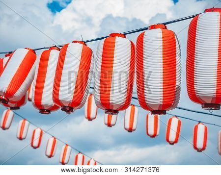 Paper Red-white Japanese Lanterns Chochin Hanging On Cloudy Blue Sky Background. Summer Background