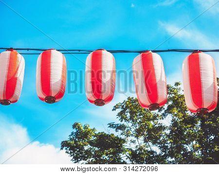 Paper Red-white Japanese Lanterns Chochin Hanging On Blue Sky Background. Summer Background