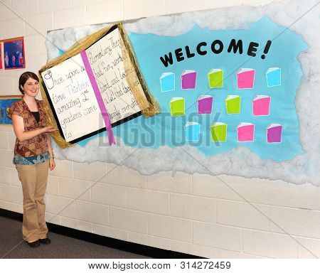 Elementary teacher prepares a bulletin board to welcome students on the first day of school.  She made a fairy tale book mounted on a blue sky with clouds. poster