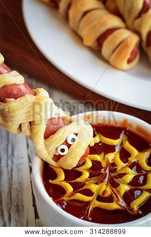 Fun Food For Kids. Mummy Hot Dogs Held Upside Down Over A Bowl Of Ketchup And Mustard Dip, With Spid