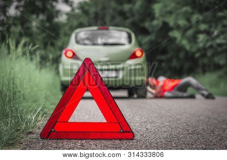 Red Warning Triangle And Broken Car On Road - Car Breakdown Concept