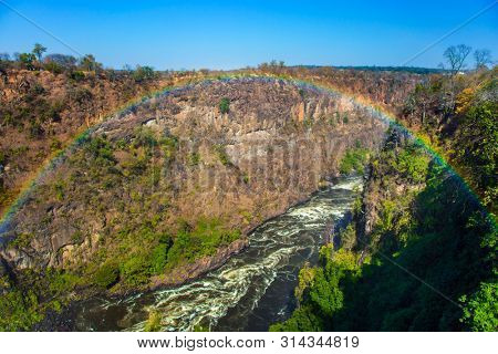 Beautiful rainbow over the turbulent African River Zambezi. The waterfall Victoria Falls located on the Zambezi River. Concept of extreme and photo tourism