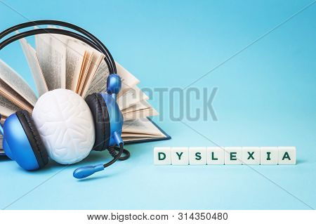 Dyslexia Word With An Open Book And Brain Stress Relief In Headphones On Blue Background, Reading Di