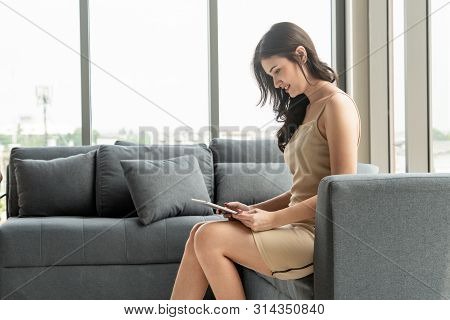 Beautiful relaxed business woman sitting on sofa couch in highrise office building tower. poster