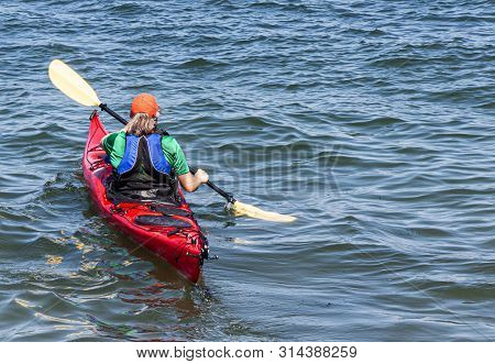 Rear View Of A Women In A Red Kayak Paddling Out Into The Bay Wearing A Blue Life Preserver And An O